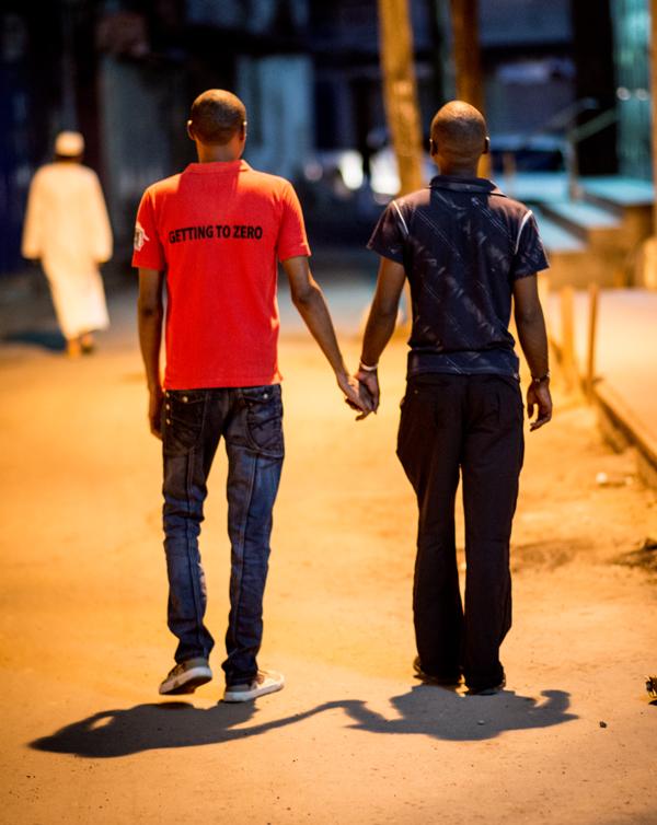Photo of two men holding hands in a dark street in Kilifi, Kenya
